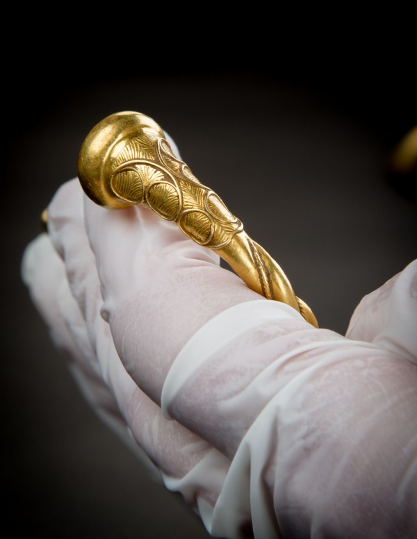gold torc handled by someone wearing gloves (Staffordshire County Council/PA)