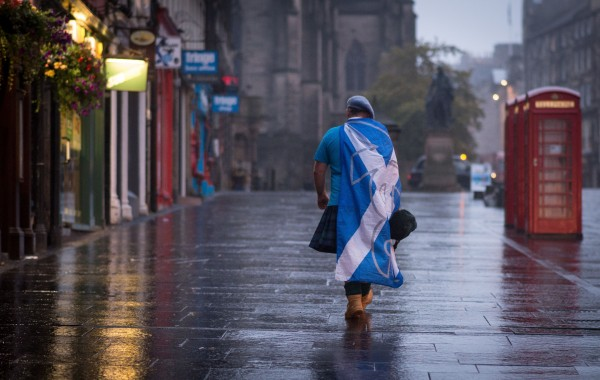 A Yes supporter walks through a rainy Edinburgh (Stefan Rousseau/PA)