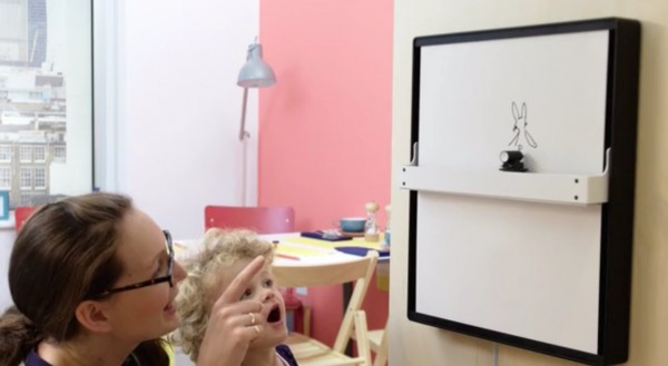 A little girl watches a drawing appear