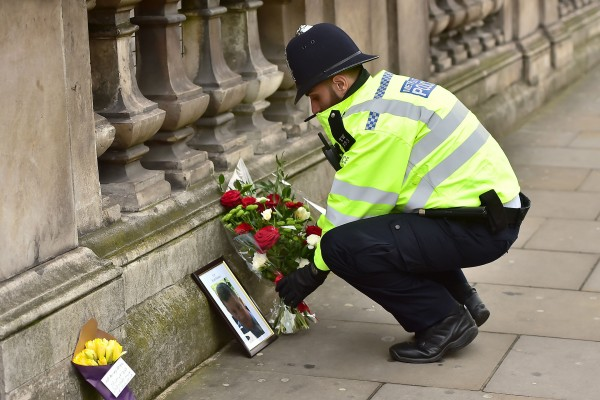 A police officer places flowers and a photo of Pc Keith Palmer on Whitehall near the Houses of Parliament in London, after seven people were arrested in raids in London, Birmingham and elsewhere linked to the Westminster terror attack (Dominic Lipinski/PA).