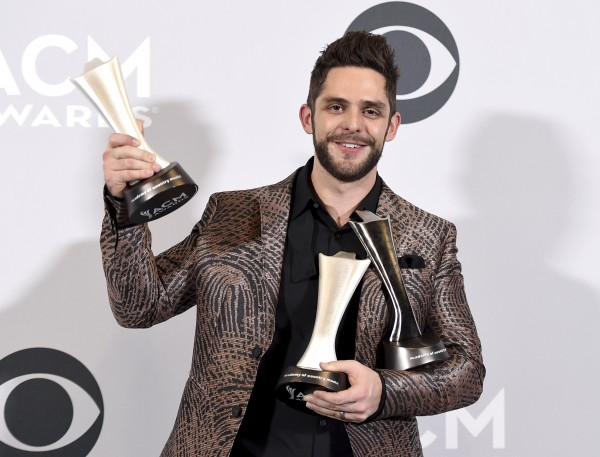 "Thomas Rhett poses in the press room with his awards for artist and songwriter for song of the year for ""Die A Happy Man,"" and male vocalist of the year at the 52nd annual Academy of Country Music Awards at the T-Mobile Arena on Sunday, April 2, 2017, in Las Vegas. (Photo by Jordan Strauss/Invision/AP)"