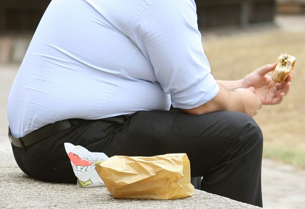 File photo dated 28/07/10 of an overweight man eating.