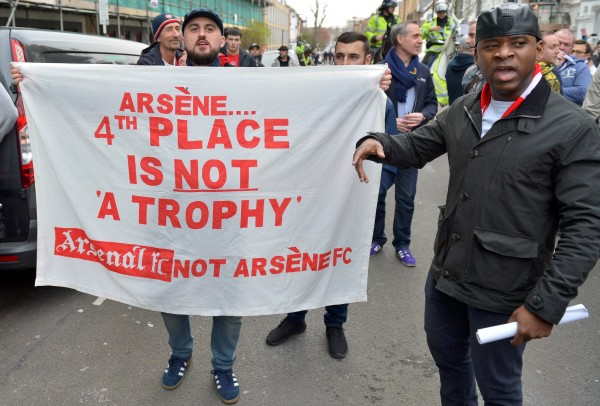 An Arsenal fan holds a sign