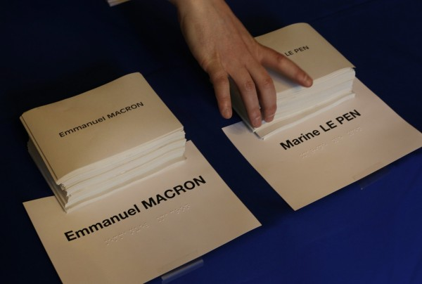 Ballot papers for the French presidential election are prepared in a polling station in Paris, Sunday, May 7, 2017.