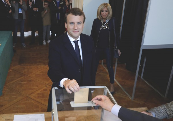 French presidential election candidate Emmanuel Macron, head of the political movement En Marche !, or Onwards ! casts his ballot at a polling station while his wife Brigitte Macron looks on, during the the second round of 2017 French presidential election, in Le Touquet, northern France, Sunday, May 7, 2017.