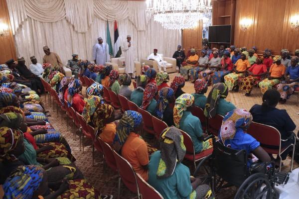 The girls are addressed by Nigerian president Muhammadu Buhari (Bayo Omoboriowo/AP)