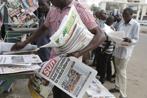 People read newspaper headlines, including stories on the names of he Nigerian Chibok kidnapped girls