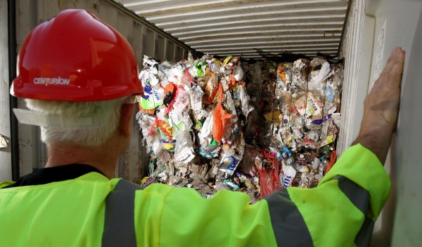 A worker looking at plastic rubbish