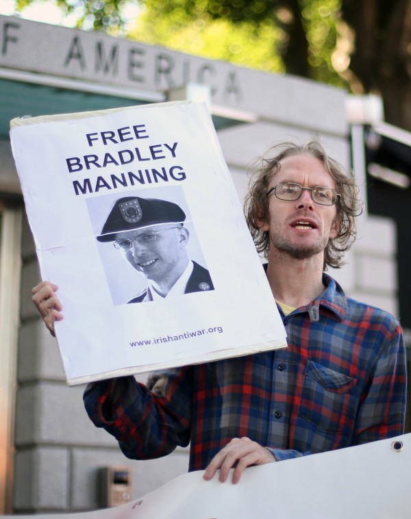 A man holds a placard as anti-war protesters mount a Free Bradley Manning demonstration at the US Embassy, Ballsbridge Dublin, the day after he was sentenced to 35 years in prison for sending classified information to WikiLeaks.