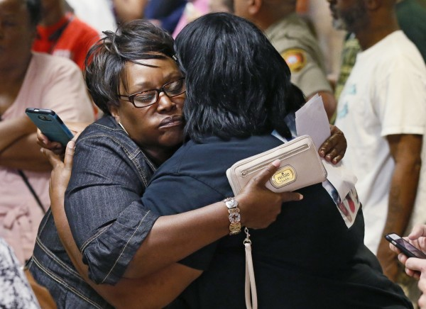 Two women embrace after leaving the courtroom