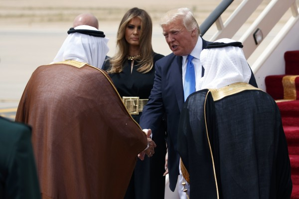U.S. President Donald Trump, top right, accompanied by first lady Melania Trump, center, shake hands