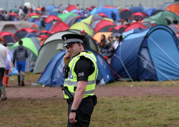 A police officer patrols in the campsite at the main stage at the T in the Park music festival at Strathallan in Perthshire.