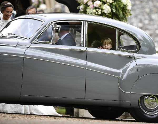Britain's Prince George waves as he leaves in a car after attending the wedding of his aunt, Pippa…