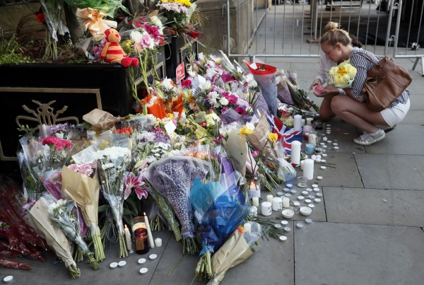 A Child Places Flowers At Memorial Site For The Victims Of