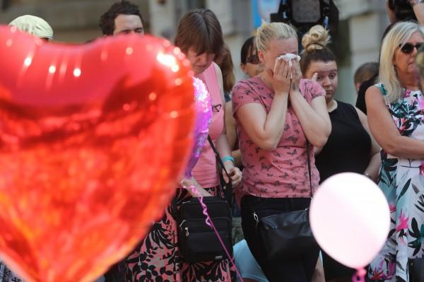 A woman cries next to a heart shaped balloon