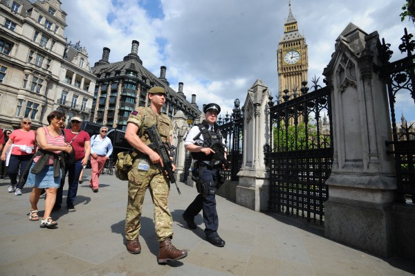 A member of the army joins police officers outside the Houses of Parliament