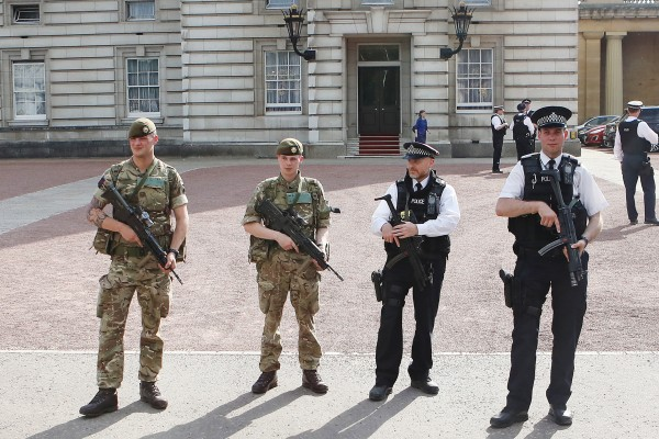 Soldiers join police officers outside Buckingham Palace.