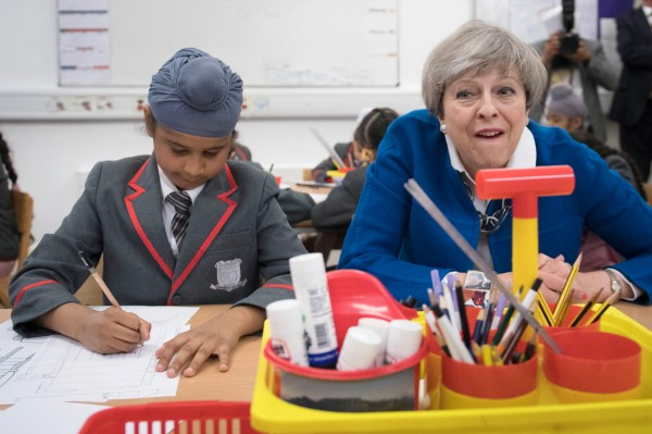 Theresa May with school children (Stefan Rousseau/PA)