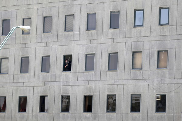An armed man can be seen in the window of the parliament building (Omid Vahabzadeh/AP)