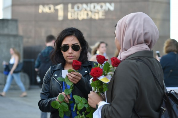 Roses with messages are given out to passers-by on London Bridge (David Mirzoeff/PA)