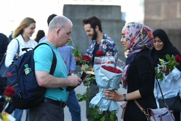 roses with messages handed out on london bridge (David Mirzoeff/PA)