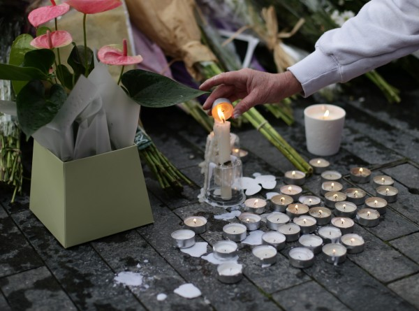 a candle being lit at a vigil in London (Yui Mok/PA)