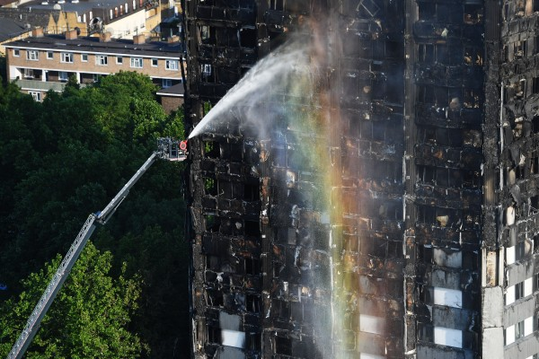 Firefighters spray water on the building (Victoria Jones/PA)