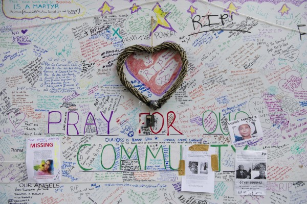 Tributes and missing posters are left on a wall near Grenfell Tower (David Mirzoeff/PA)