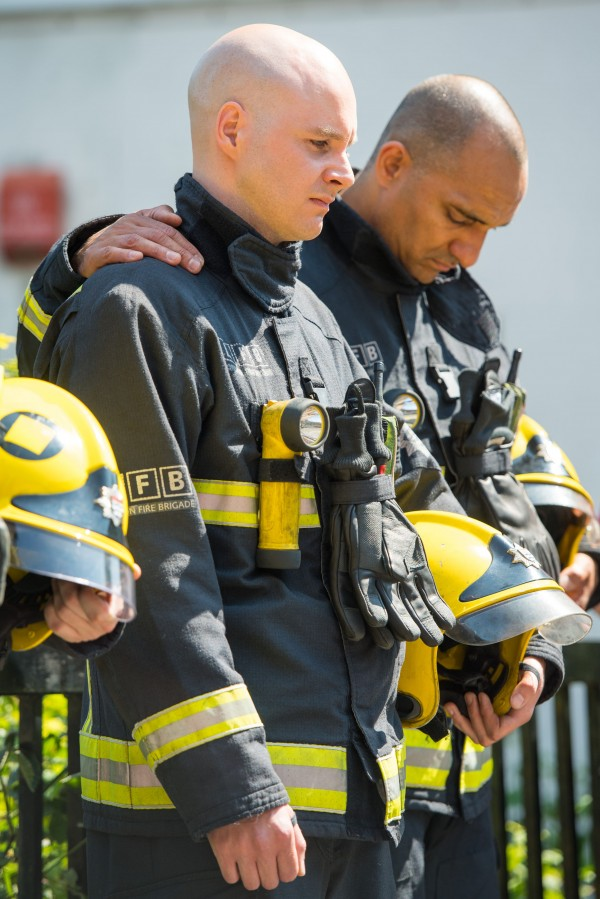 Firefighters observe a minute's silence near Grenfell Tower (Dominic Lipinski/PA)