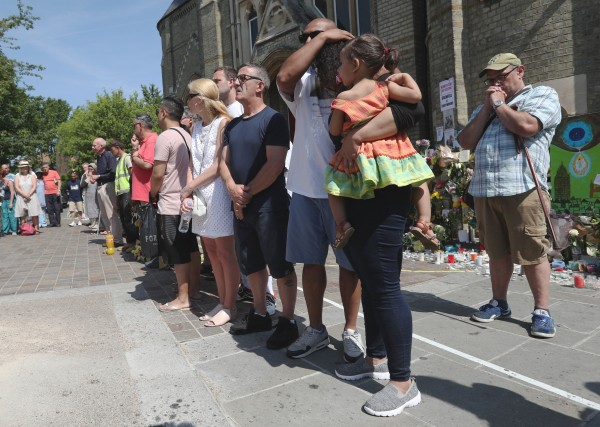 People observe a minute's silence near Grenfell Tower (Jonathan Brady/PA) Wire