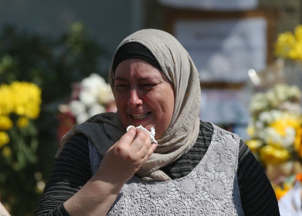 A woman appears emotional after a minute's silence (Jonathan Brady/PA)