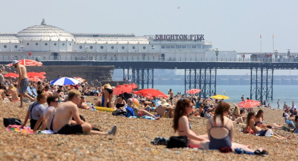 People enjoy the hot weather on the beach in Brighton (Gareth Fuller/PA)