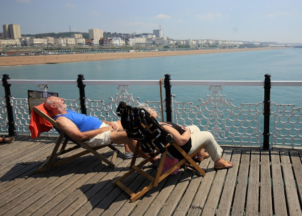 A couple enjoy the hot weather on the pier in Brighton (Gareth Fuller/PA)