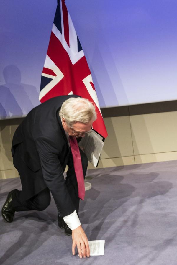 David Davis reaches down to pick notes off the floor (Geert Vanden Wijngaert/AP)