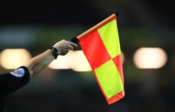 A match official raises the offside flag