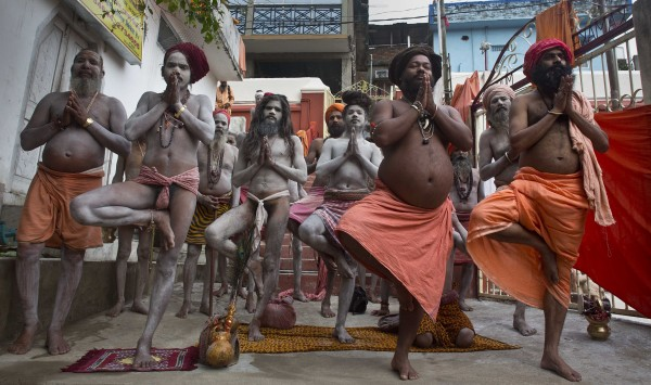 Hindu holy men perform Yoga as others follow to mark the International Yoga Day at Kamakhya temple in Gauhati, India (Anupam Nath/AP)
