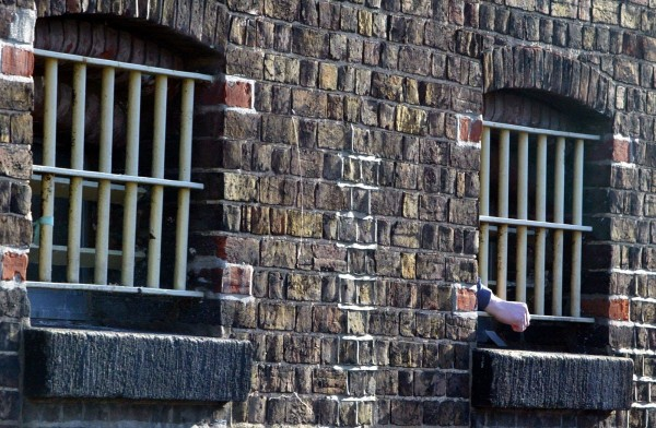 A prisoners hand pokes through the bars.